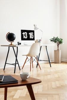 Echtes foto eines couchtisches mit notebooks und tasse mit schreibtisch, globus, computer und stuhl im hintergrund in einem home-office-interieur