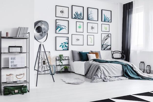 Echtes foto eines gemütlichen bettes neben einer schwarzen lampe in einem monochromen schlafzimmer mit regalen mit ornamenten und postern an der wand