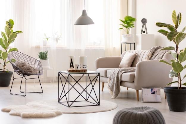 Echtes foto eines schwarzen tisches neben einem beigen sofa und einem sessel im gemütlichen wohnzimmer mit pflanzen um sie herum