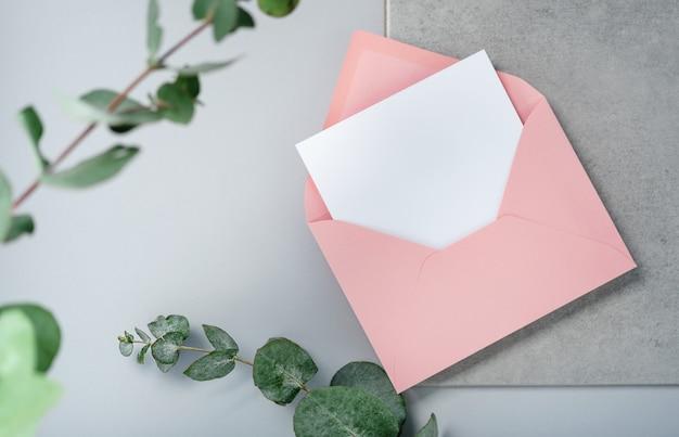 Echtes foto. quadratisches einladungskartenmodell des rosa umschlags mit einem eukalyptuszweig. draufsicht mit kopierraum, hellgrauer hintergrund. vorlage für branding und werbung