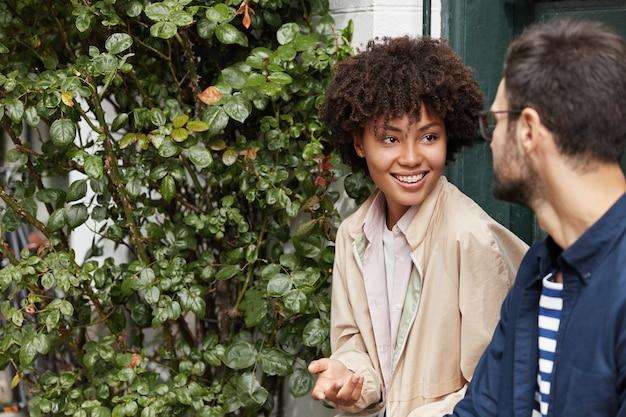 Echtes kommunikationskonzept. positives junges ehepaar gemischter rassenfreunde genießt freizeit, hat spaß und redet miteinander