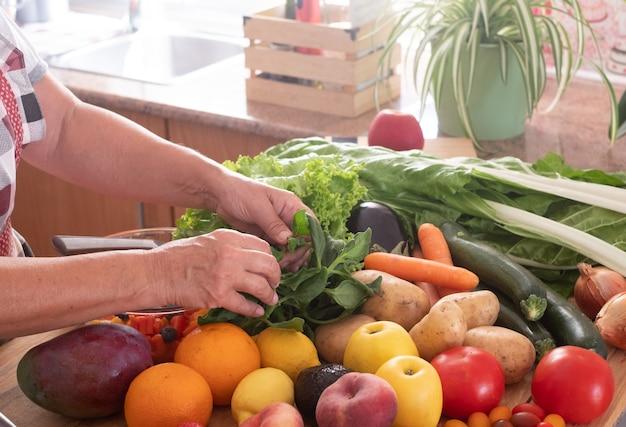Ecke der küche und zwei hände einer älteren frau, die an einem frischen obstsalat arbeitet. holztisch mit einer großen gruppe von bunten obst und gemüse. gesundes essen