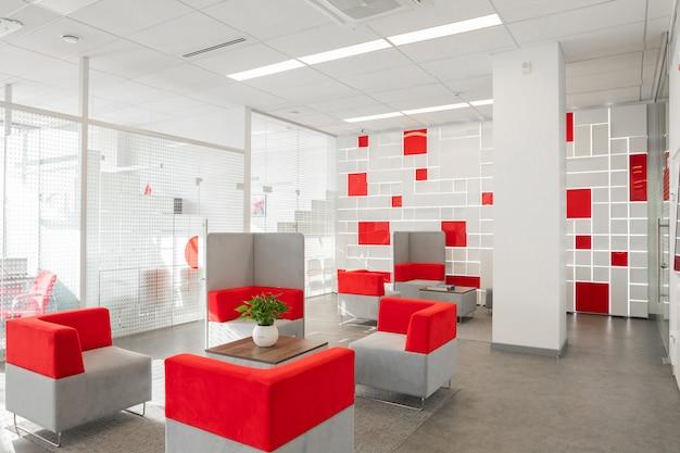 Ecke des modernen büros mit weißen wänden, grauem boden, offenem raumbereich mit den roten und weißen lehnsesseln und räumen hinter glaswand