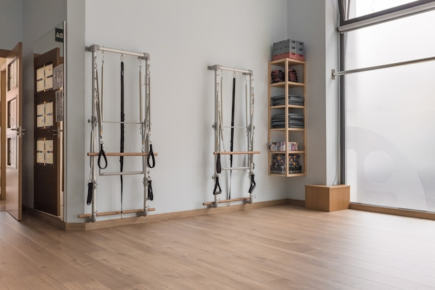 Ecke eines pilates-studios mit zwei geräten und einem regal. holzboden und fenster