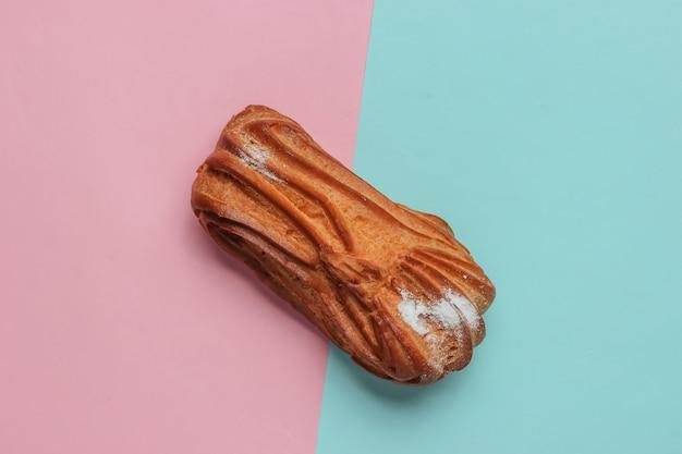 Eclair auf einem bluepink-pastellhintergrund minimalistisches lebensmittelstillleben