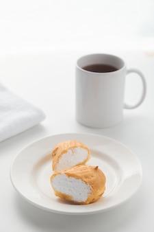 Eclair-kuchen im puddingschnitt liegt auf einem weißen teller mit einem glas im hintergrund.