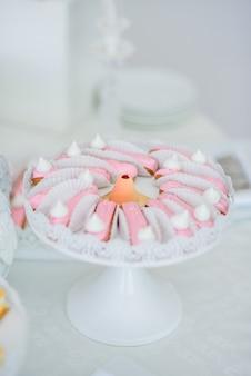 Eclairs, die mit rosa glasur bedeckt wurden, dienten auf runder weißer platte
