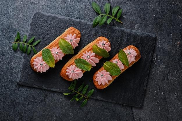 Eclairs mit rosa creme, verziert mit minzblättern. dessert auf einer schwarzen schieferplatte. kuchen auf dunklem hintergrund.