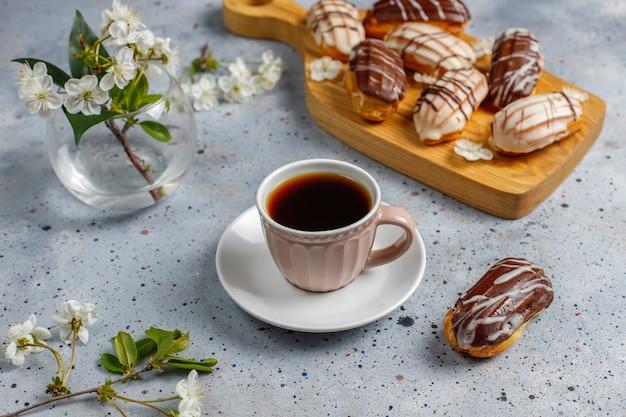 Eclairs oder kränzchen mit schwarzer schokolade und weißer schokolade mit pudding im inneren, traditionelles französisches dessert.