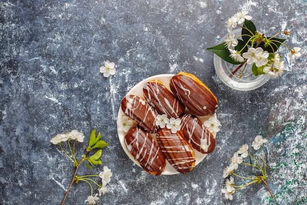 Eclairs oder kränzchen mit schwarzer schokolade und weißer schokolade mit pudding im inneren