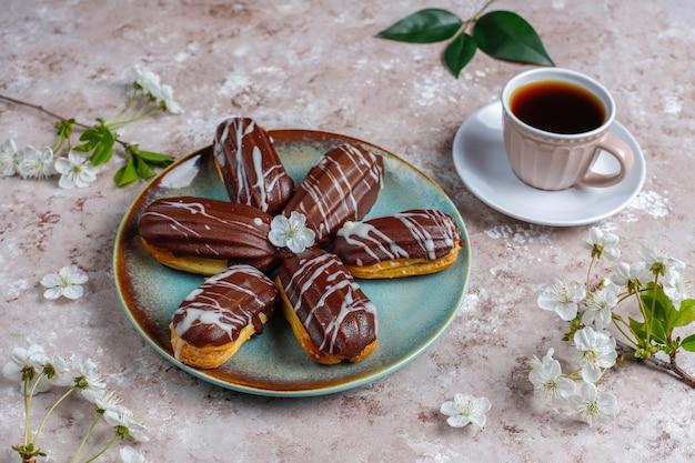 Eclairs oder kränzchen mit schwarzer schokolade und weißer schokolade mit vanillepudding im inneren, traditionelles französisches dessert.