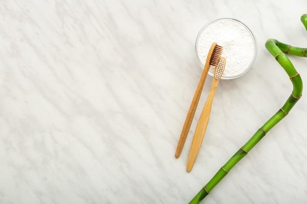 Eco bambuszahnbürste bambuspflanze zahnputzmittel zahnpulver auf weißem marmorhintergrundflach