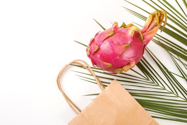 Eco-einkaufstasche und drachenfrucht auf weißem hintergrund. exotische tropische früchte, palmblätter.