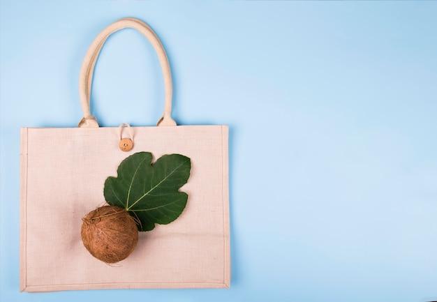 Eco freundliche baumwolltasche mit kokosnuss und blatt von feigen auf einem pastellblau, copyspace, minimale naturart