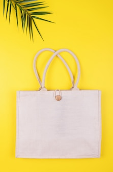 Eco freundliche baumwolltasche mit palmblatt auf einem gelb, copyspace, minimale naturart. umweltschutz recycling