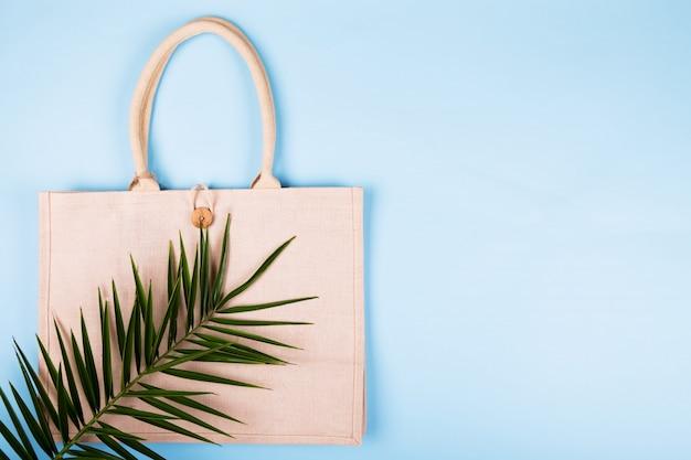 Eco freundliche baumwolltasche mit palmblatt auf einem pastellblau, copyspace, minimale naturart. umweltschutz recycling