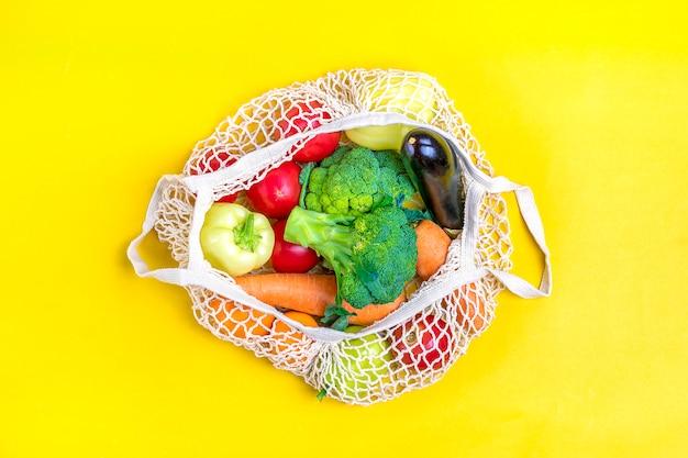 Eco freundliche maschenshoptasche mit organischem grünem gemüse auf gelb. flachgelegt, draufsicht.