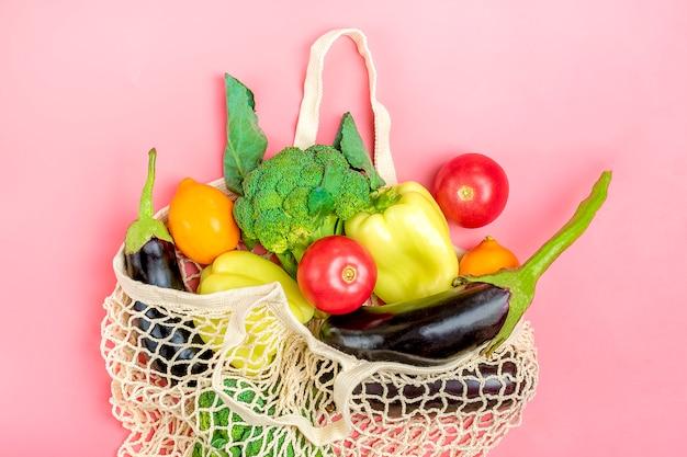 Eco freundliche maschenshoptasche mit organischem grünem gemüse auf rosa. flachgelegt, draufsicht.