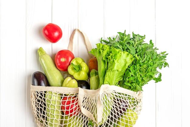 Eco freundliche maschenshoptasche mit organischem grünem gemüse auf weißem holz