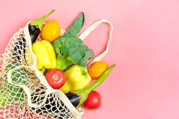 Eco freundliche mesh-shop-tasche mit bio-grünem gemüse auf rosa
