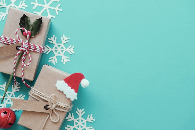 Eco geschenkboxen mit weihnachtsschneeflockendekoration auf grünem pastellhintergrund