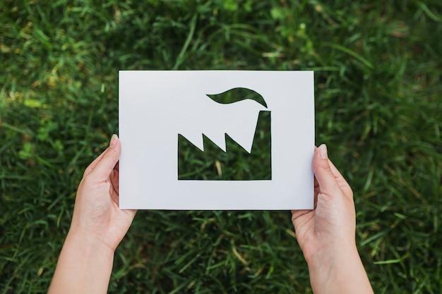 Eco-konzept mit den händen, die herausgeschnittenes papier zeigt fabrik halten