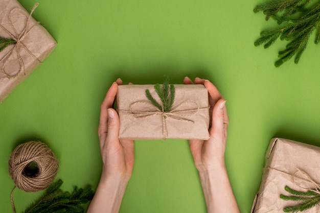 Eco vorhanden mit grünpflanzen im kraftpapier in den händen auf einer grünen oberfläche