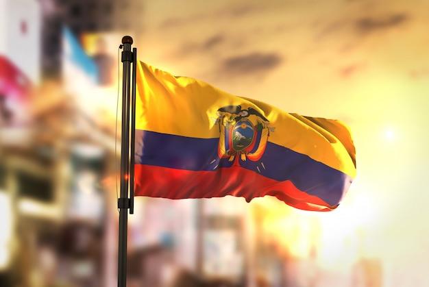 Ecuador flagge gegen stadt verschwommen hintergrund bei sonnenaufgang hintergrundbeleuchtung
