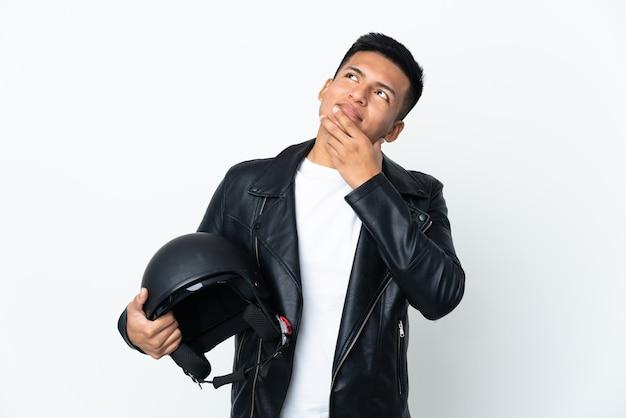 Ecudorianischer mann mit einem motorradhelm lokalisiert auf weißem hintergrund, der beim lächeln nach oben schaut