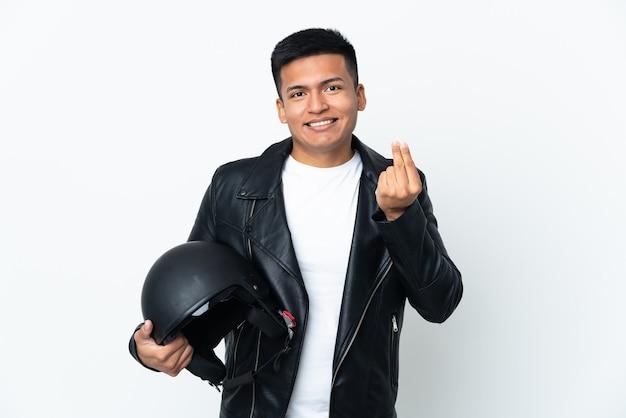 Ecudorianischer mann mit einem motorradhelm lokalisiert auf weißer wand, die geldgeste macht