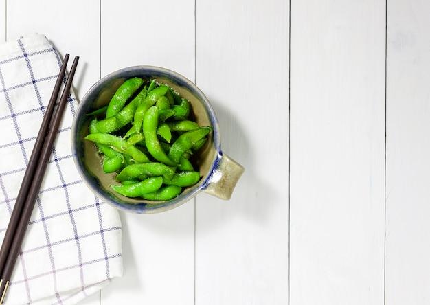 Edamame knabbert, gekochte grüne sojabohnen, japanisches essen, draufsicht auf weißen holztisch