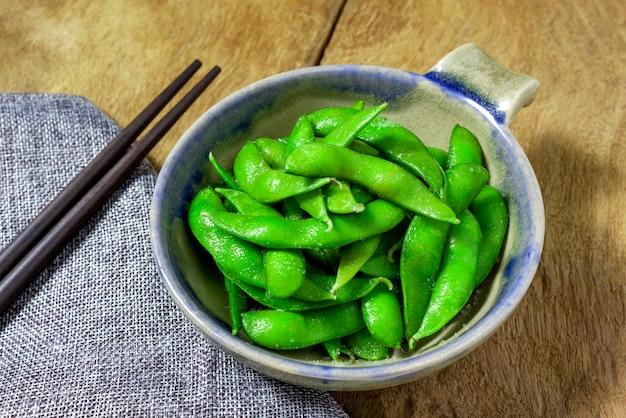 Edamame knabbert, kochte grüne sojabohnen, japanisches lebensmittel, draufsicht über holztisch