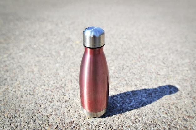 Edelstahl-edelstahl-eco-thermo-wasserflasche mit mockup auf asphalt seien sie plastikfrei zero waste copy space zero waste keine plastik nachhaltigkeit