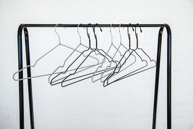 Edelstahl kleiderstange mit leeren kleiderbügeln gegen eine weiße wand, teil ab