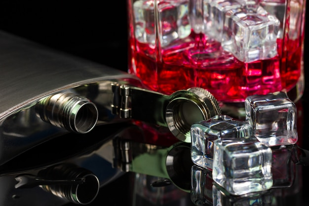 Edelstahlflaschenalkoholalkohol und -eis auf tabelle mit rotem whisky im glas auf dunkelheitshintergrund