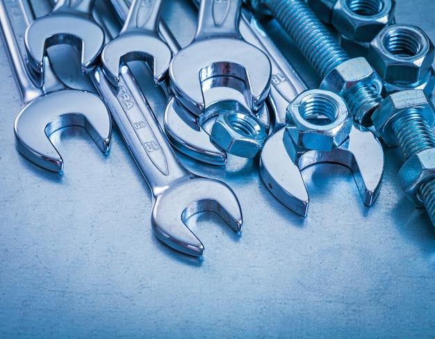 Edelstahlschlüssel schraubenschlüssel und schraubenmuttern auf metallischem hintergrund reparaturkonzept