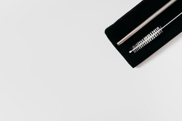 Edelstahlstrohhalme und reinigungsbürste auf schwarzem beutel
