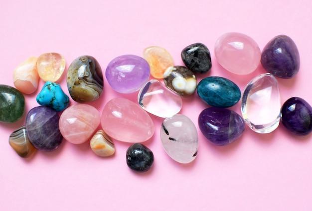 Edelsteine in verschiedenen farben. amethyst, rosenquarz, achat, apatit, aventurin, olivin, türkis, aquamarin, bergkristall auf rosa hintergrund