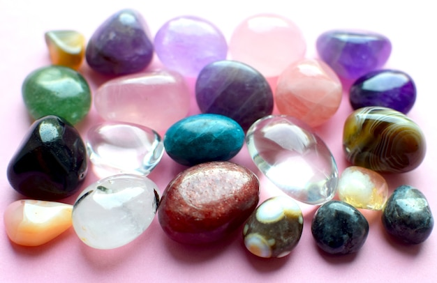 Edelsteine in verschiedenen farben. amethyst, rosenquarz, achat, apatit, aventurin, olivin, türkis, aquamarin und bergkristall auf rosa hintergrund