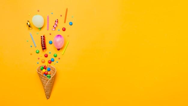 Edelsteine; sträusel; luftschlangen; kerzen und ballon über dem waffelkegel auf gelbem hintergrund