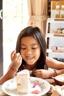 Eeating kuchen des asiatischen mädchens im café.