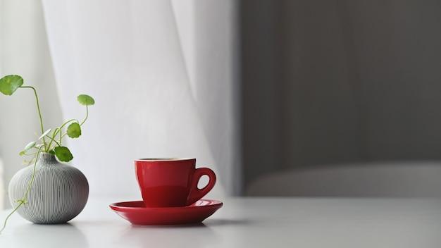 Efeu in vase und roter kaffeetasse aus keramik mit untersetzern auf dem weißen modernen schreibtisch über dem vorhang im wohnzimmer
