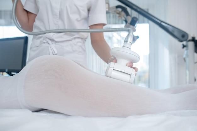 Effektives verfahren. ärzte hände in handschuhen halten den apparat über bein des patienten auf der couch liegend