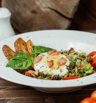 Egg benedict serviert mit brotcrackern und grünem salat