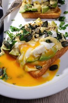Eggs benedict auf toast mit holländischer sauce, avocadoscheiben