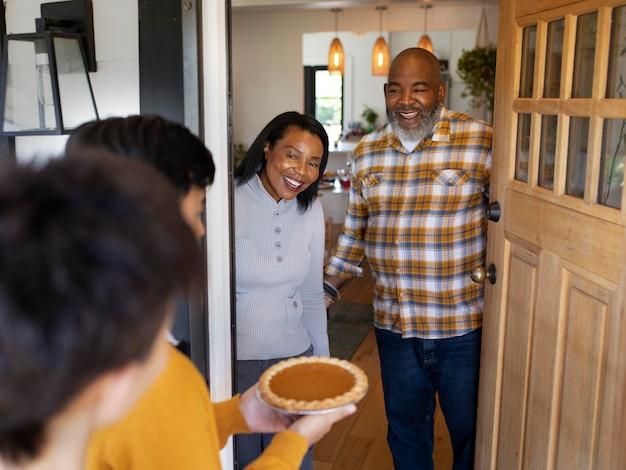 Ehefrau und ehemann begrüßen verwandte zum thanksgiving-dinner