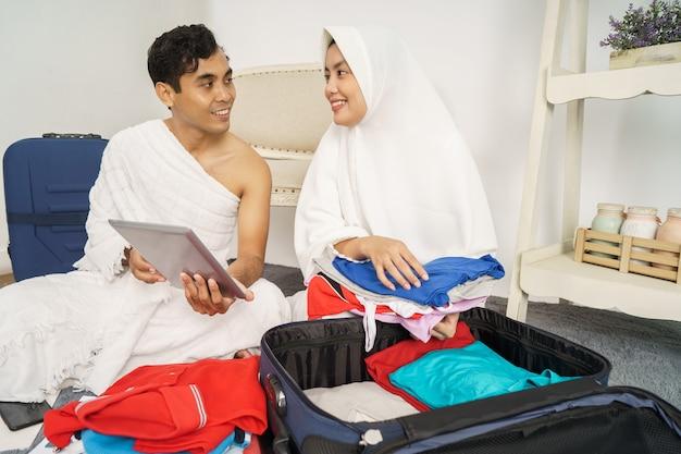 Ehefrau und ehemann muslimischer pilger bereiten gegenstände für den besuch des hajj in der kaaba vor