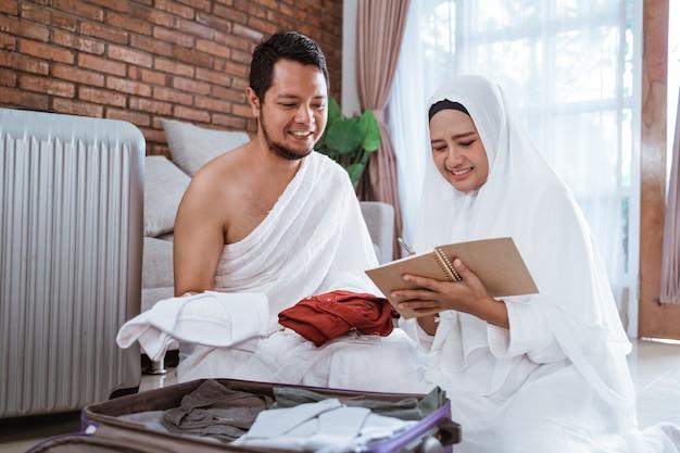 Ehefrau und ehemann muslimischer pilger bereiten gegenstand vor