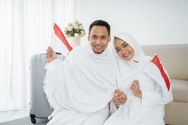 Ehefrau und ehemann muslimischer pilger mit indonesischer flagge