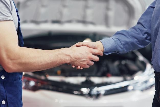 Ehemann automechaniker und kundin vereinbaren die reparatur des autos
